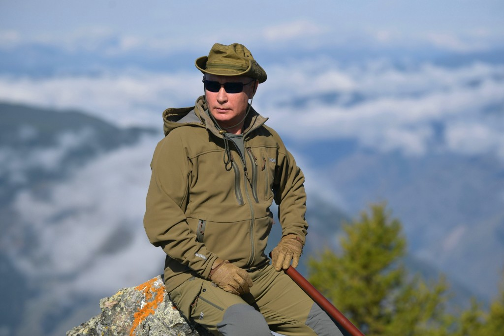FILE In this undated file photo released by Russian Presidential Press Service, Russian President Vladimir Putin rests on a hill in Siberia during a b...