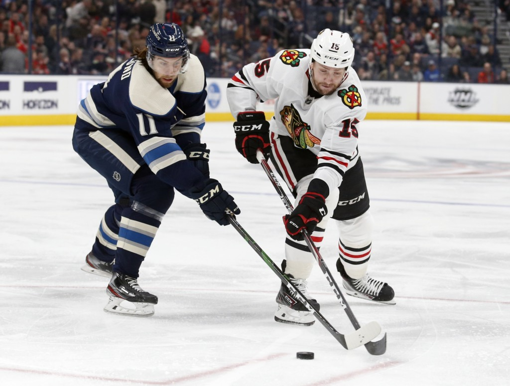 Columbus Blue Jackets forward Kevin Stenlund, left, of Sweden, and Chicago Blackhawks forward Zack Smith chase the puck during the second period of an...