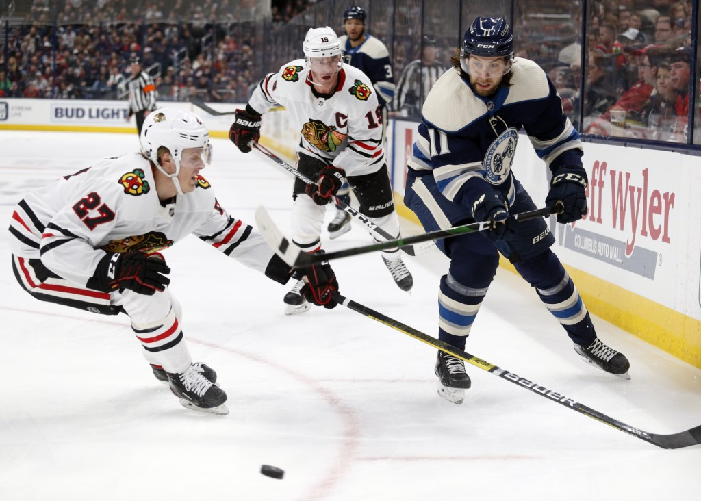 Columbus Blue Jackets forward Kevin Stenlund, right, of Sweden, passes the puck in front of Chicago Blackhawks defenseman Adam Boqvist, left, of Swede...