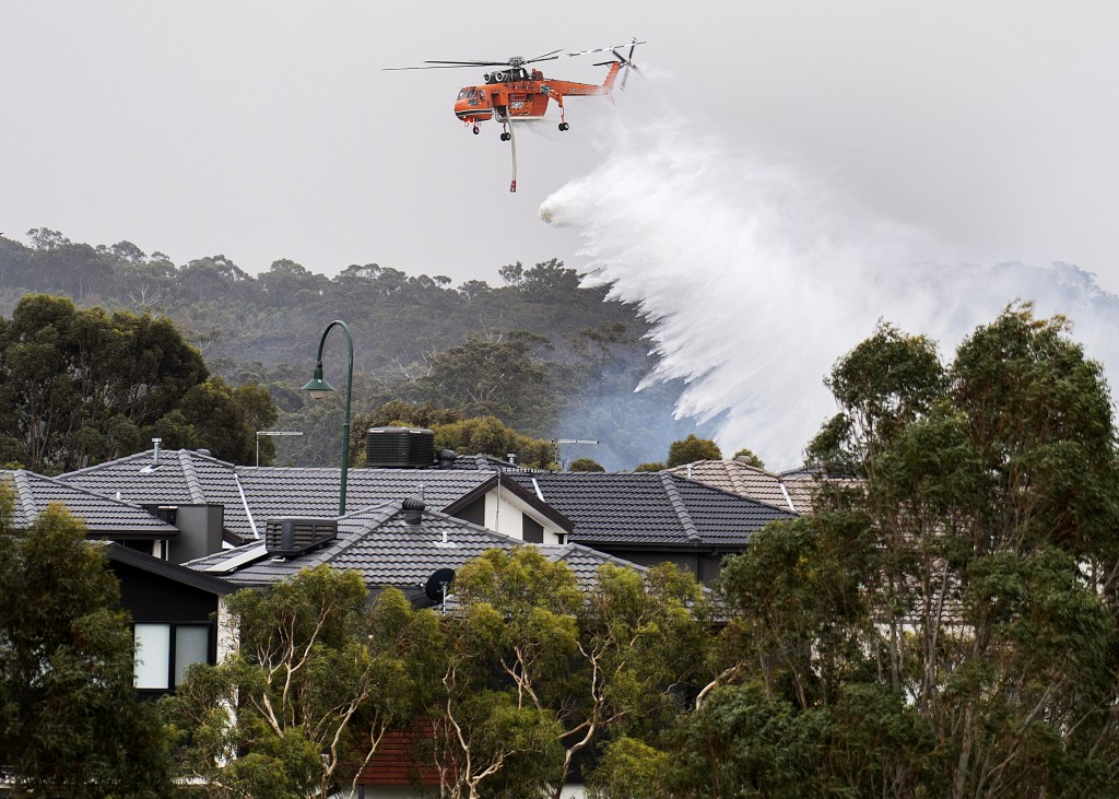 A skycrane drops water on a bushfire in scrub behind houses in Bundoora, Melbourne, Monday, Dec. 30, 2019. New Year's Eve fireworks in Australia's cap...