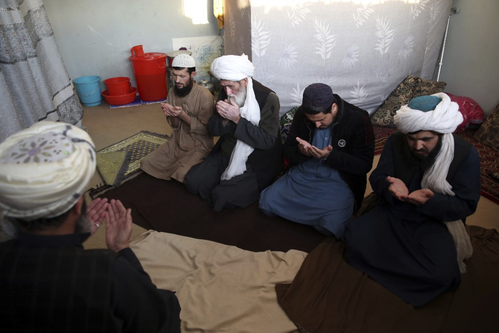 In this Saturday, Dec. 14, 2019, photo, jailed Taliban pray inside the Pul-e-Charkhi jail after an interview with The Associated Press in Kabul, Afgha...
