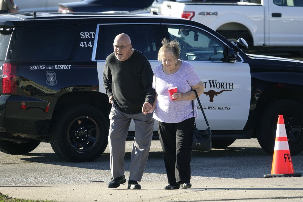 An elderly couple walks from West Freeway Church of Christ hours after a fatal shooting at the church, Sunday, Dec. 29, 2019, in White Settlement, Tex...