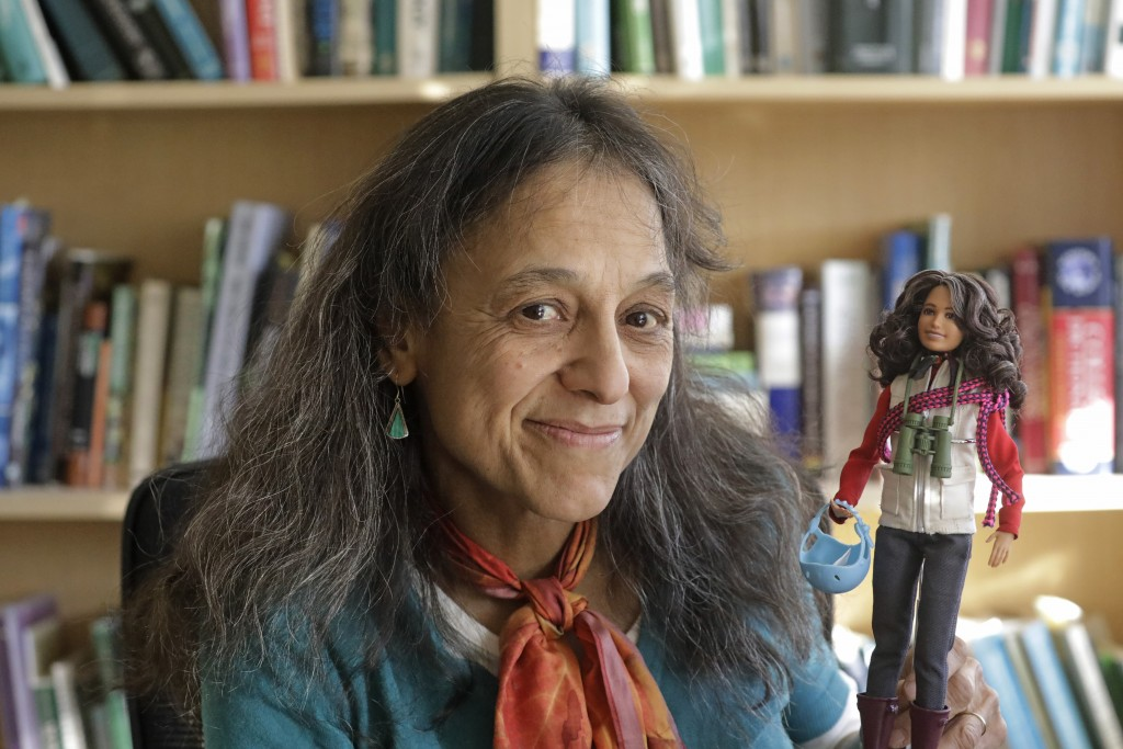 This Dec. 3, 2019, photo, ecologist Nalini Nadkarni is shown in her lab on the University of Utah campus in Salt Lake City holding a Barbie created to...