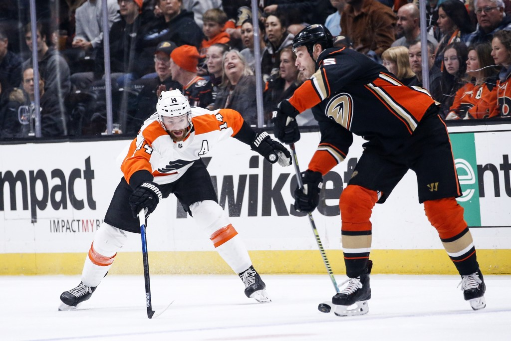 Philadelphia Flyers forward Sean Couturier, left, tries to stop a shot by Anaheim Ducks defenseman Korbinian Holzer during the first period of an NHL ...