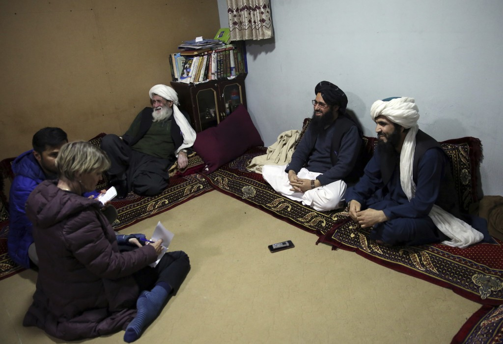 In this Saturday, Dec. 14, 2019, photo, Maulvi Niaz Mohammad, 45, second right, speaks during an interview with The Associated Press inside the Pul-e-...