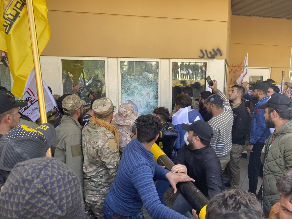 Protesters smash a window inside the U.S. embassy compound, in Baghdad, Iraq, Tuesday, Dec. 31, 2019. Dozens of angry Iraqi Shiite militia supporters ...