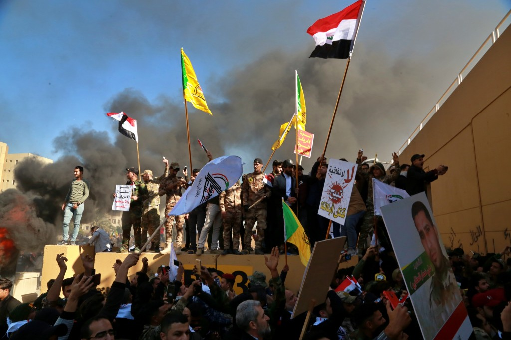 Protesters burn property in front of the U.S. embassy compound, in Baghdad, Iraq, Tuesday, Dec. 31, 2019. Dozens of angry Iraqi Shiite militia support...