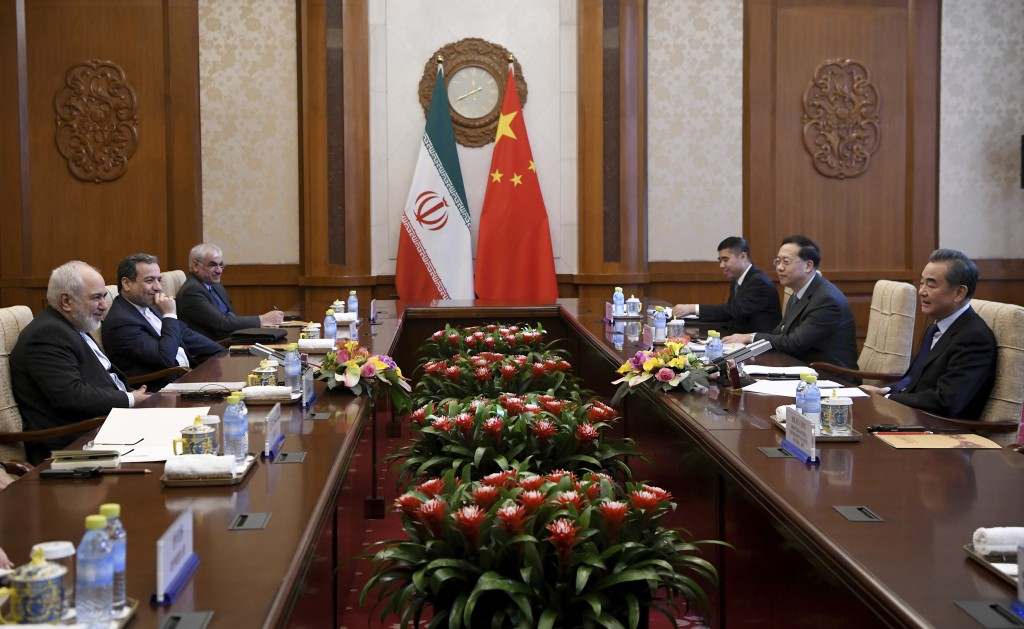 China's Foreign Minister Wang Yi, right, talks to Iran's Foreign Minister Mohammad Javad Zarif, left, during a meeting at the Diaoyutai state guest ho...
