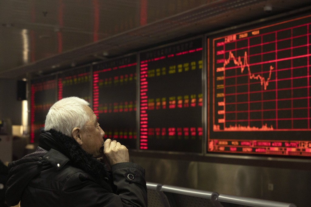An investor monitors stock prices at a brokerage in Beijing on Tuesday, Dec. 31, 2019. Asian shares were lower in quiet New Year's Eve trading, with m...