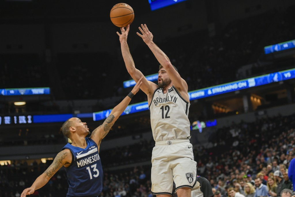 Brooklyn Nets guard Joe Harris (12) shoots over Minnesota Timberwolves guard Shabazz Napier (13)during the first half of an NBA basketball game Monda...