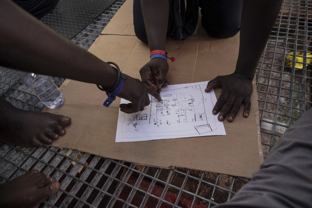 In this Sept. 23, 2019 photo, rescued migrants draw a map of the Zawiya, Libya detention center run by the al-Nasr Martyrs militia. Migrants at the ce...