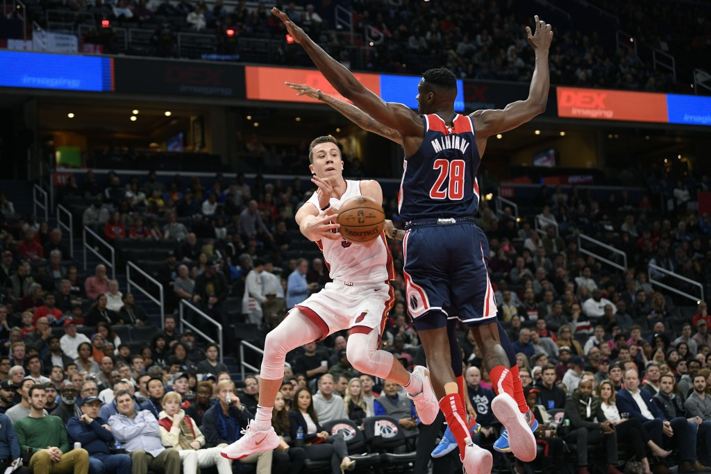 Miami Heat forward Duncan Robinson, left, passes the ball against Washington Wizards center Ian Mahinmi (28) during the first half of an NBA basketbal...