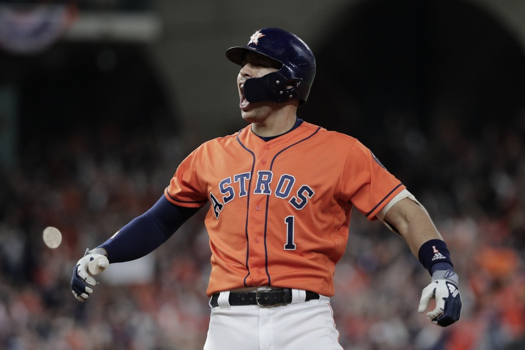 FILE - In this Oct. 30, 2019, file photo, Houston Astros' Carlos Correa reacts to his RBI-single during the fifth inning of Game 7 of the baseball Wor...