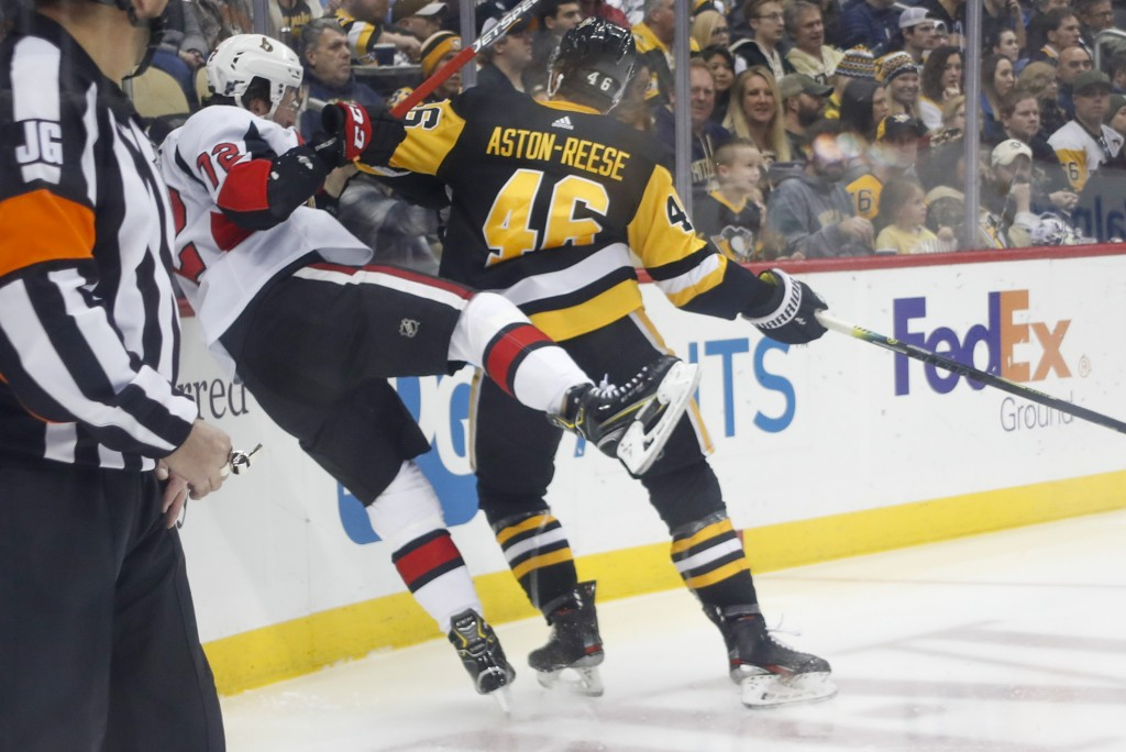Pittsburgh Penguins' Zach Aston-Reese (46) checks Ottawa Senators' Thomas Chabot (72) toward the boards during the second period of an NHL hockey game...
