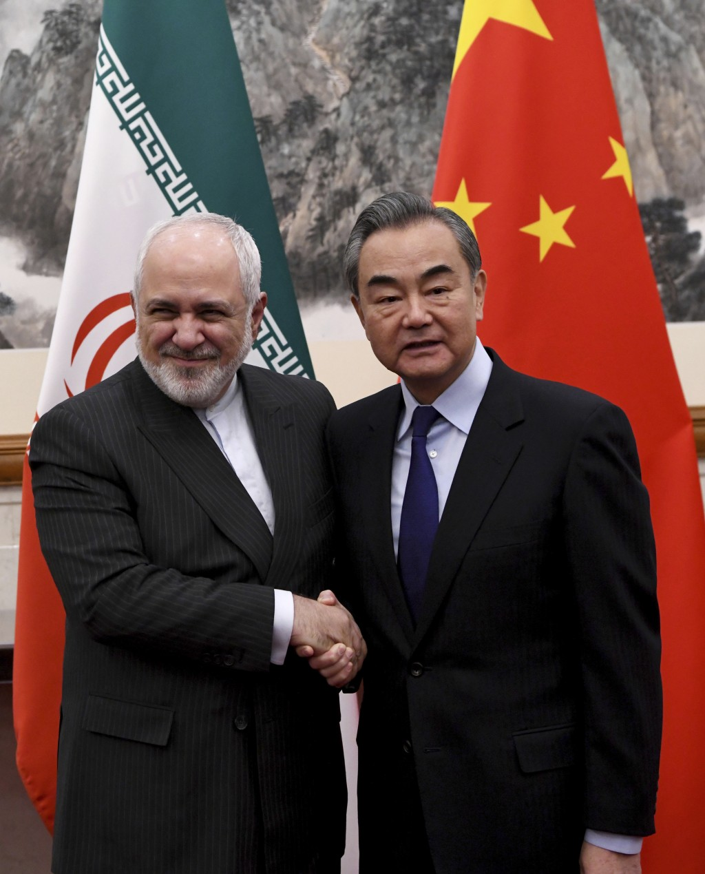 China's Foreign Minister Wang Yi, right, shakes hands with Iran's Foreign Minister Mohammad Javad Zarif during a meeting at the Diaoyutai state guest ...