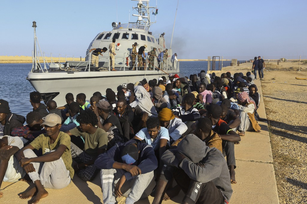 FILE - In this Tuesday, Oct. 1, 2019 file photo, rescued migrants are seated next to a coast guard boat in the city of Khoms, Libya, around 120 kilome...