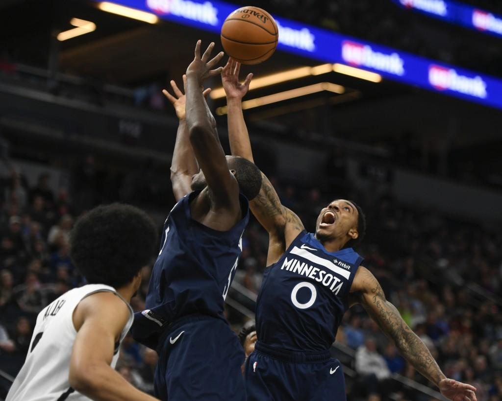 Minnesota Timberwolves guard Jeff Teague(0) and center Gorgui Dieng reach for a rebound against the Brooklyn Nets during the first half of an NBA bas...