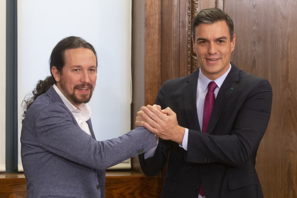 Spain's caretaker Prime Minister Pedro Sanchez, right and Podemos party leader Pablo Iglesias clasp hands after signing an agreement between the two p...