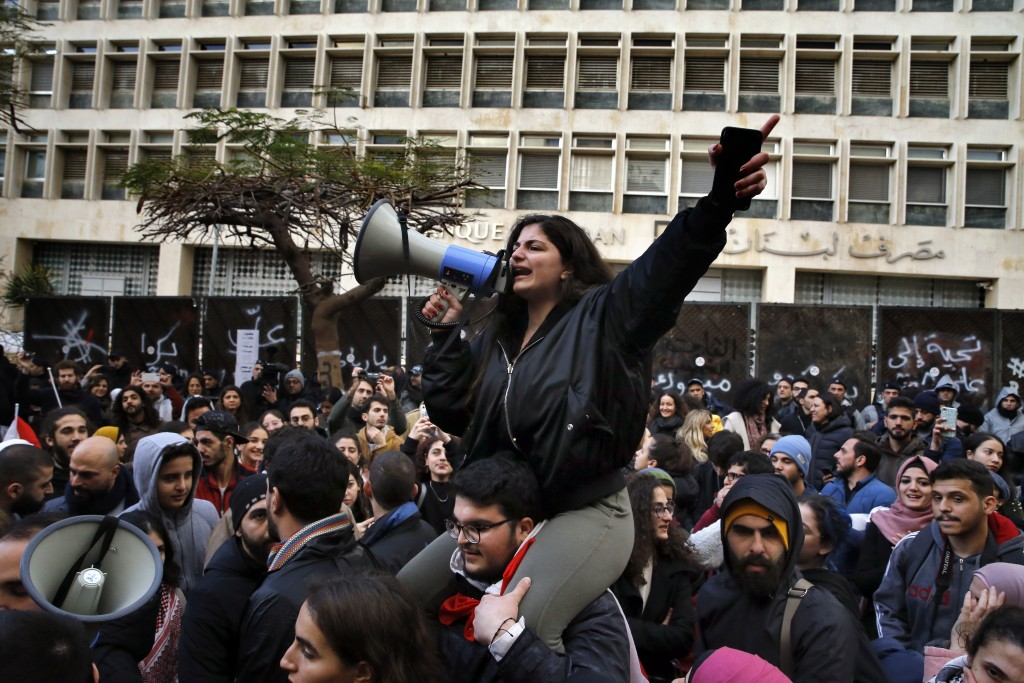 A protester leads a chant during ongoing protests against the Lebanese political class, in front of the Central Bank, in Beirut, Lebanon, Monday, Dec....