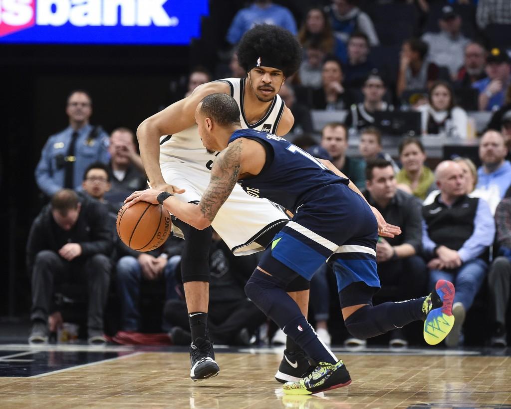 Brooklyn Nets center Jarrett Allen, top, defends as Minnesota Timberwolves guard Shabazz Napier tries to get past him during the first half of an NBA ...