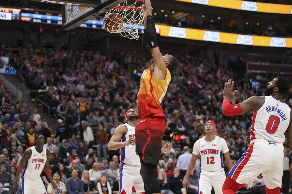 Utah Jazz center Rudy Gobert (27) dunks the basketball with Detroit Pistons guard Bruce Brown (6) watching during the third quarter of an NBA basketba...