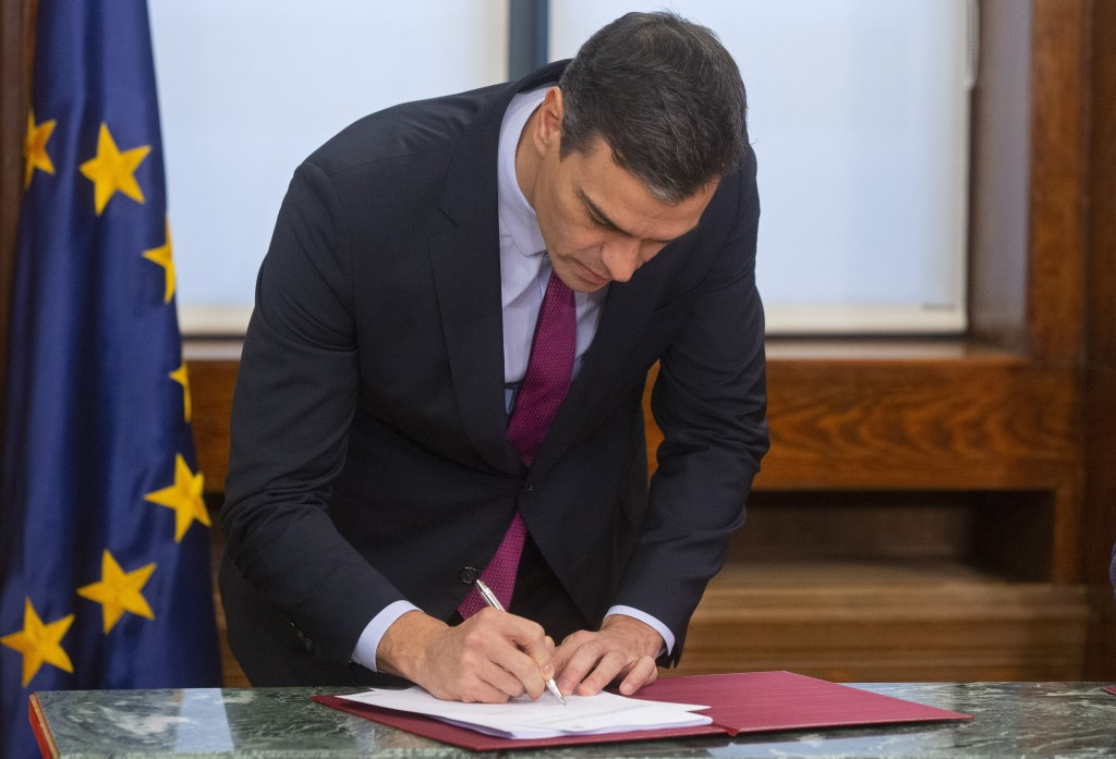 Spain's caretaker Prime Minister Pedro Sanchez signs an agreement with the Podemos party in the Spanish parliament in Madrid, Spain, Monday, Dec. 30, ...