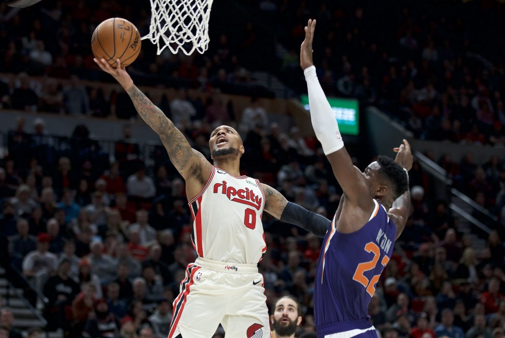 Portland Trail Blazers guard Damian Lillard, left, shoots over Phoenix Suns center Deandre Ayton during the second half of an NBA basketball game in P...