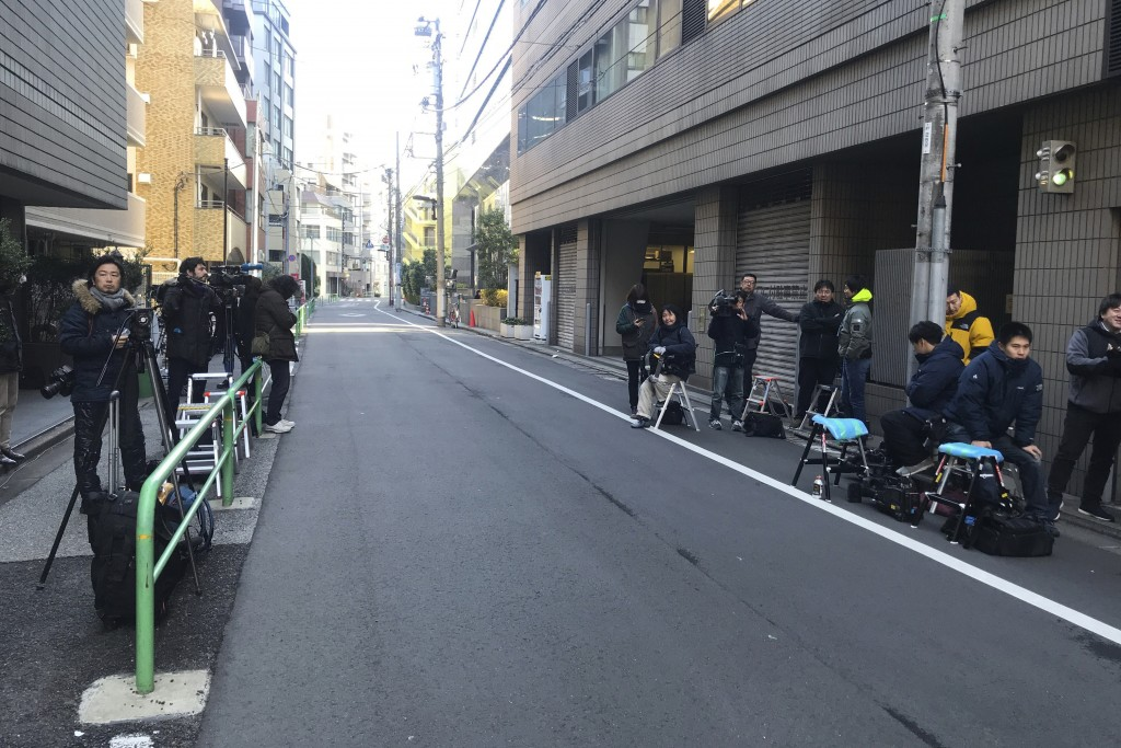 Journalists stake out at the back entrance of a building which houses an office of Junichiro Hironaka, a lawyer for Nissan's former Chairman Carlos Gh...