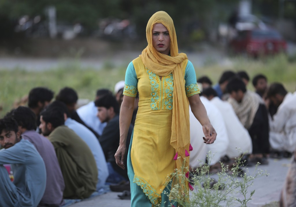 FILE - In this May 27, 2019 file photo, a Pakistani transgender person provides food to people during the Muslim fasting month of Ramadan, in Islamaba...