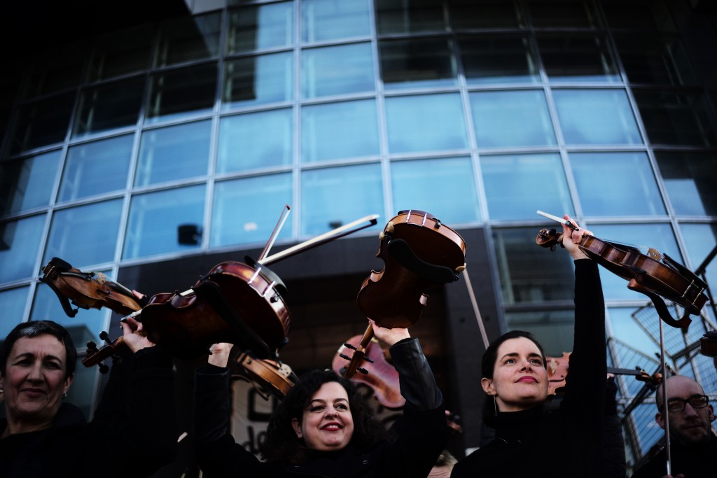 Striking musicians of the Paris Opera house hold their violins after performing outside the Bastille Opera house Tuesday, Dec. 31, 2019 in Paris. (AP ...
