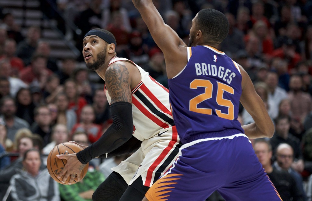 Portland Trail Blazers forward Carmelo Anthony, left, drives to the basket around Phoenix Suns forward Mikal Bridges during the second half of an NBA ...