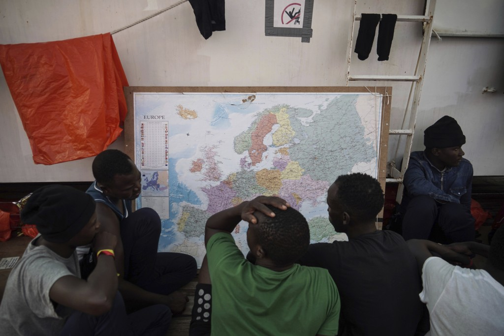 In this Sept. 23, 2019 photo, rescued migrants look at a map of Europe aboard the Ocean Viking humanitarian ship as it sails in the Mediterranean Sea....