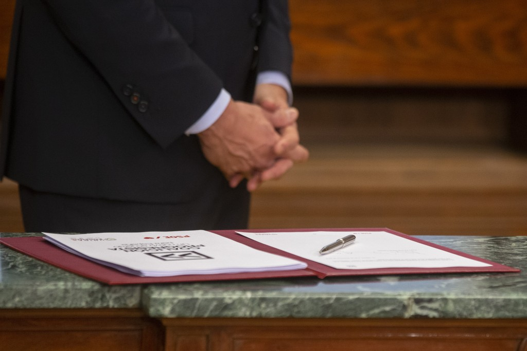 Spain's caretaker Prime Minister Pedro Sanchez, stands by an agreement signed with the Podemos party in the Spanish parliament in Madrid, Spain, Monda...