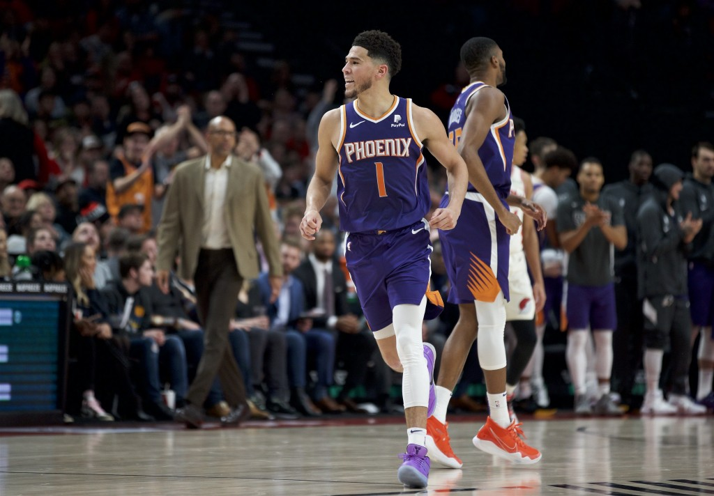 Phoenix Suns guard Devin Booker reacts after scoring against the Portland Trail Blazers during the second half of an NBA basketball game in Portland, ...