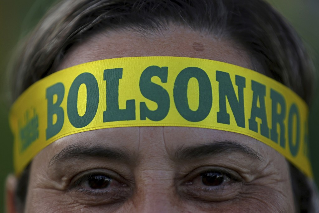 FILE - In this Oct. 28, 2018 file photo, a supporter of presidential front-runner Jair Bolsonaro wears a headband supporting his candidate as he waits...