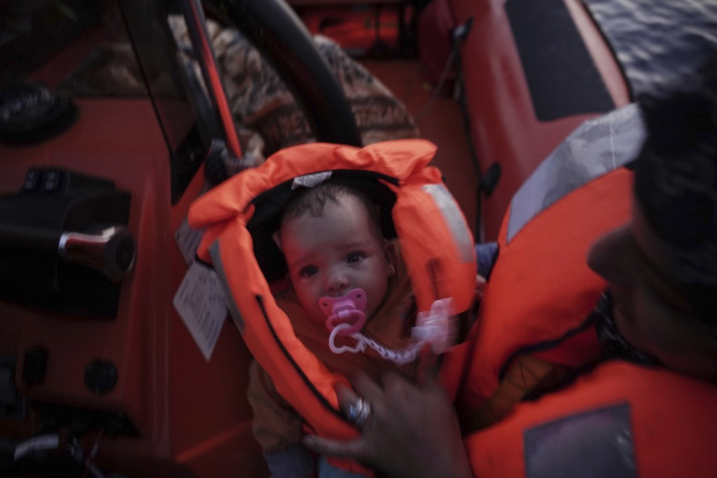 In this Sept. 19, 2019 photo, 4-month-old Mira is held by her mother during a rescue by the Ocean Viking humanitarian ship in the Mediterranean Sea. H...