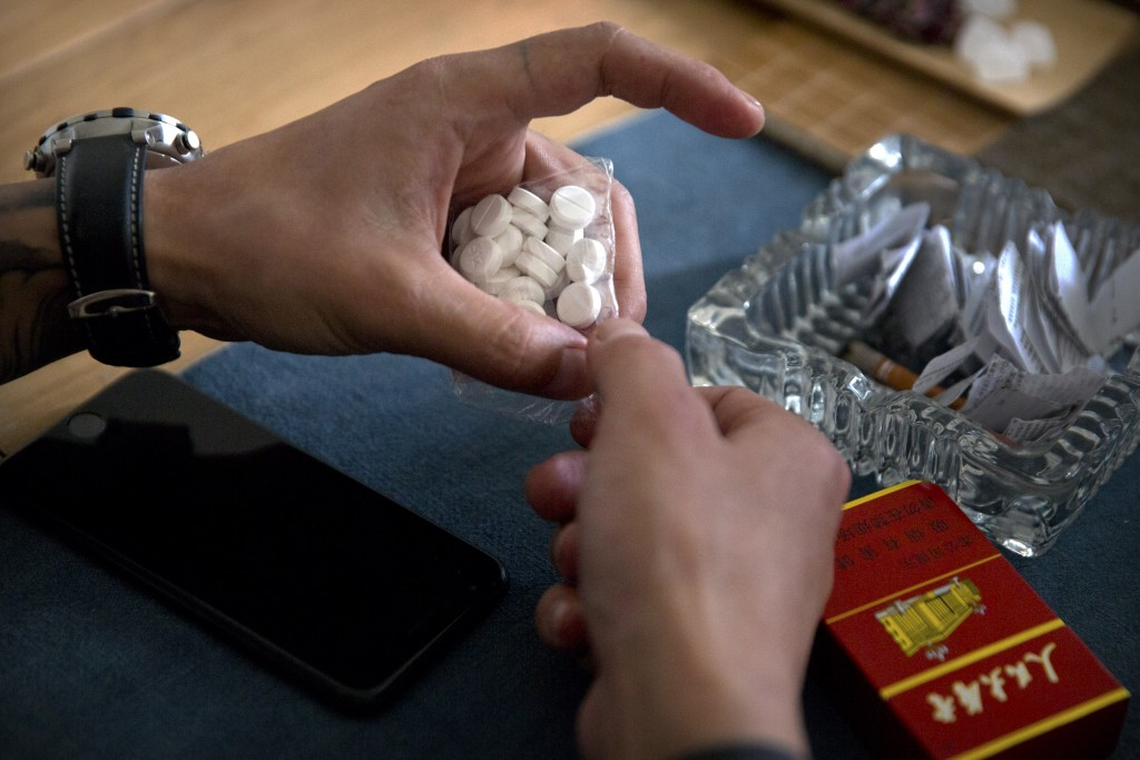 In this March 28, 2019, photo, Yin Hao, who also goes by Yin Qiang, opens a package of Tylox pills he earlier purchased illicitly in a tea house in Xi...