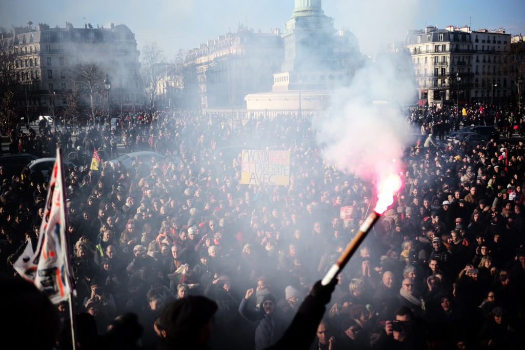 A worker holds a flare after a crowd on the Place de la Bastille listened to striking musicians of the Paris Opera house performing outside the Bastil...