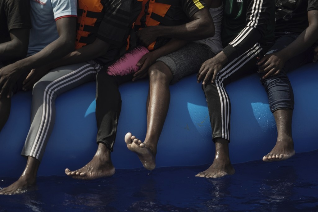 In this Sept. 17, 2019 photo, migrants sit on an overcrowded rubber boat as they wait to be rescued by the Ocean Viking humanitarian ship run by SOS M...