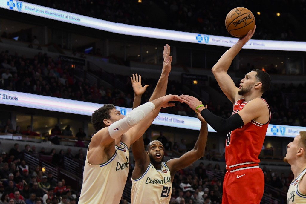 Chicago Bulls guard Zach LaVine (8) shoots past Milwaukee Bucks forward Khris Middleton (22) and center Brook Lopez, left, during the first half of an...