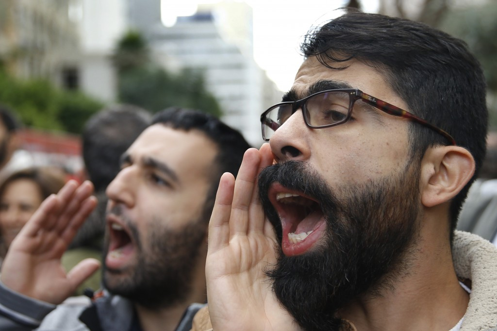 Protesters chant slogans during ongoing protests against the Lebanese political class, in front of the Central Bank, in Beirut, Lebanon, Monday, Dec. ...
