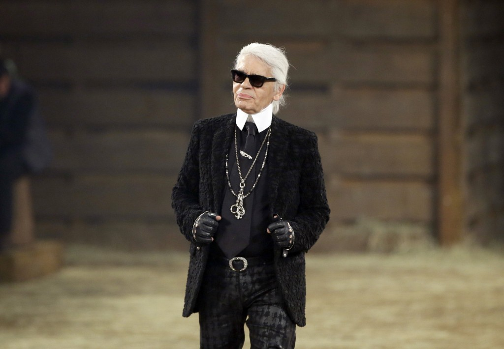 Designer Karl Lagerfeld takes a bow at the end of his Metiers d'Art fashion show in Dallas on Dec. 10, 2013. Lagerfeld, whose trademark white ponytail...
