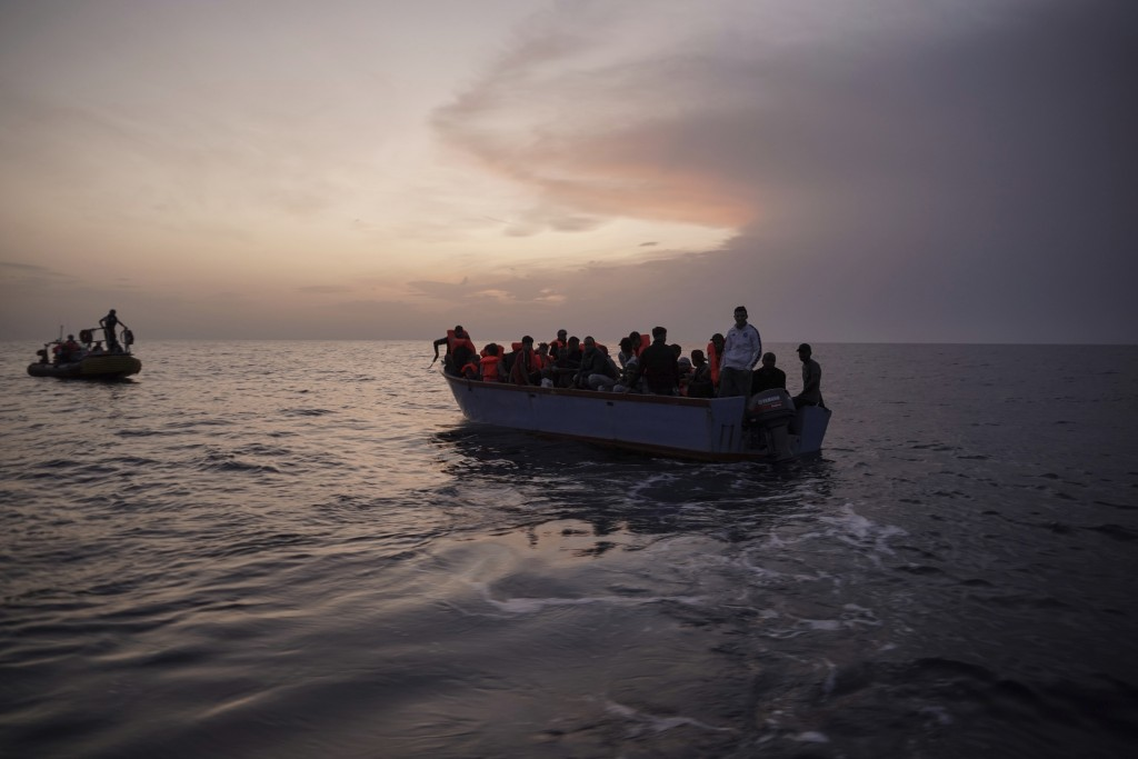 In this Sept. 19, 2019 photo, migrants on an overcrowded wooden boat wait to be rescued by the Ocean Viking humanitarian ship in the Mediterranean Sea...