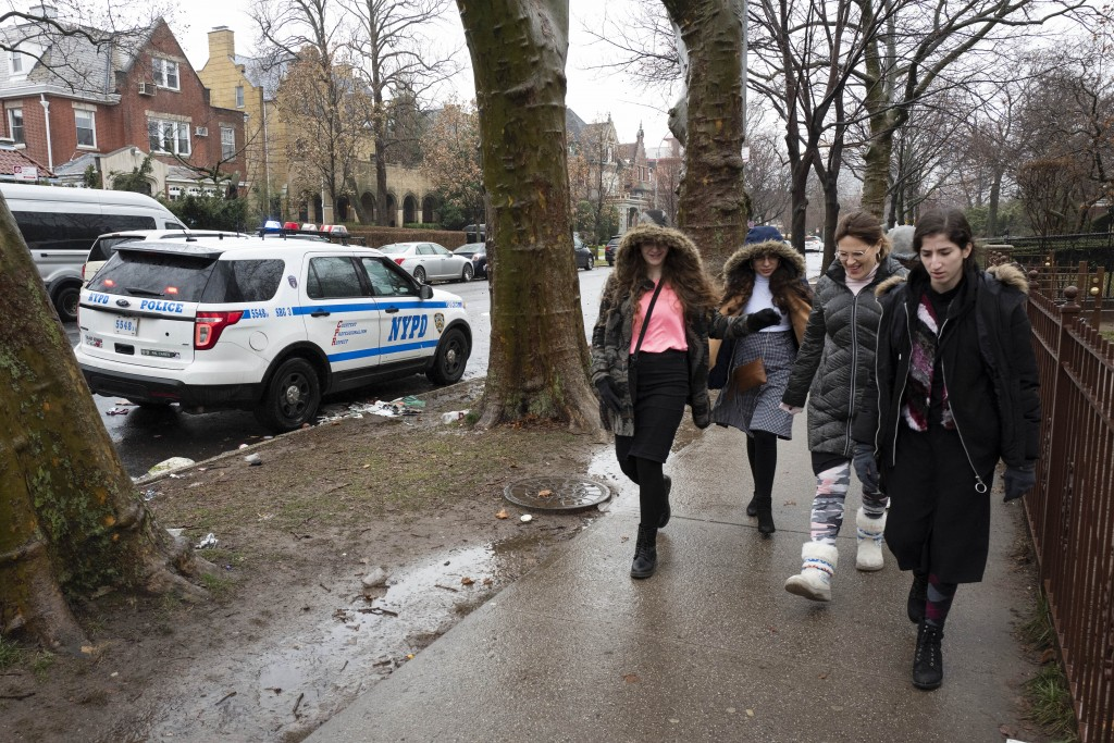 Jewish girls walk by a police car stationed in the Crown Heights neighborhood, Monday, Dec. 30, 2019 in the Brooklyn borough of New York. Police have ...