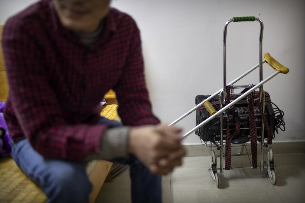 In this Dec. 5, 2019 photo, Wu Yi, who has struggled with Oxycontin abuse, sits in his rented room near his crutch and the portable amplifier he uses ...