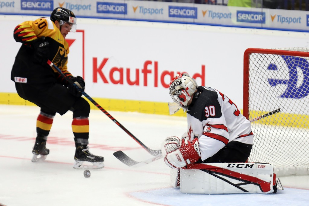 Germany's Justin Schuetz vies for the puck with Canada's goalkeeper Joel Hofer, during the 2020 IIHF World Junior Ice Hockey Championships Group B mat...