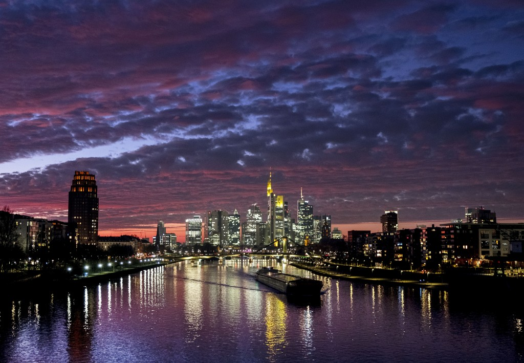 A cargo ship passes the buildings of the banking district on the river Main in Frankfurt, Germany, Monday, Dec. 30, 2019. (AP Photo/Michael Probst)