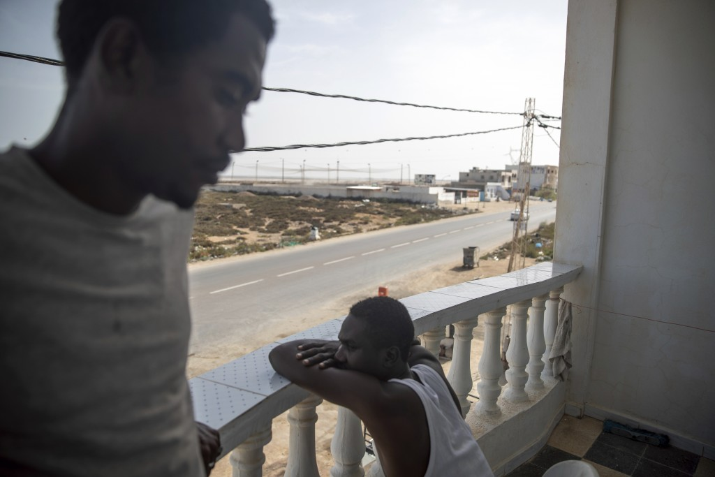 In this Monday, Sept. 23, 2019 photo, Sudanese migrants who tried crossing the Mediterranean from Libya sit in a balcony in a Tunisian Red Crescent fa...