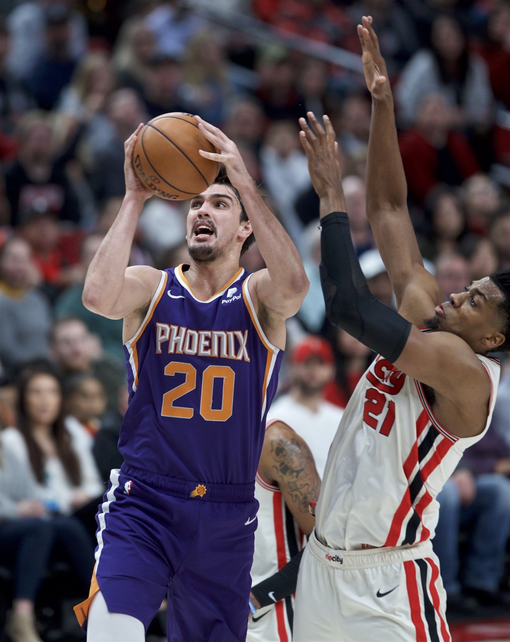 Phoenix Suns forward Dario Saric, left, shoots over Portland Trail Blazers center Hassan Whiteside during the second half of an NBA basketball game in...