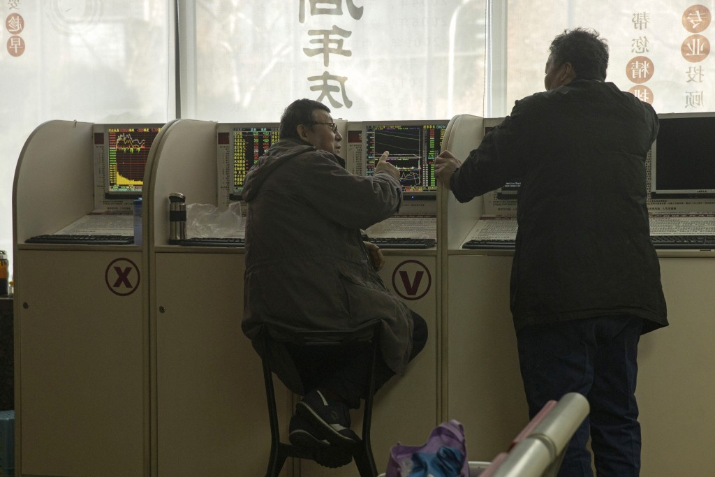 Investors monitor stock prices at a brokerage in Beijing on Tuesday, Dec. 31, 2019. Asian shares were lower in quiet New Year's Eve trading, with many...